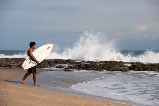 """Cruz Townsend, of Port St. Lucie, carries his surfboard to the water's edge as he heads into the water at Bathtub Beach on Friday, Nov. 15, 2019, in Stuart. """"It's definitely rougher than I expected,"""" said Townsend of the surf conditions. Heavy surf conditions and safety concerns required closure of Bathtub Beach."""