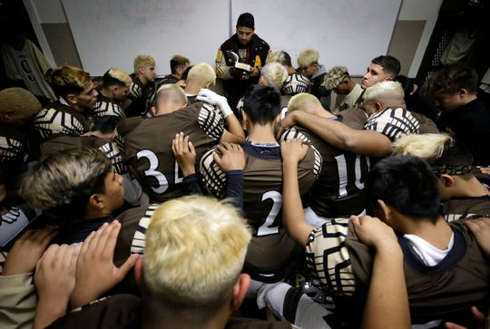 Austin High School has a prayer before their playoff game Thursday against Hanks.
