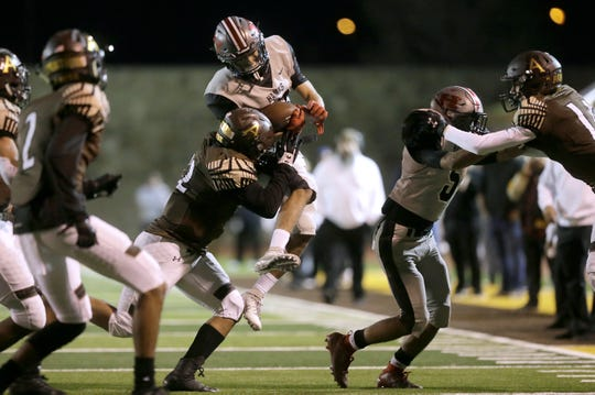 Hanks receiver Mykal Blanco is hit by Austin linebacker Sergio Rodriguez during their playoff game Thursday at Austin High School.