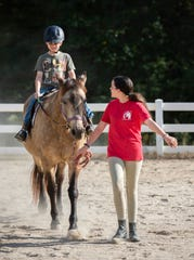Meghan O'Hare walks a horse as Deklan Corrigan rides during a lesson at Eden Farms.