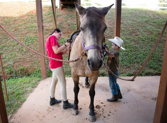Meghan O'Hare, left, and Deklan Corrigan prepare a horse for a riding lesson at Eden Farms.