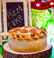 Shareable menu items at Bowlero include pizza cake, measuring 9 inches tall.