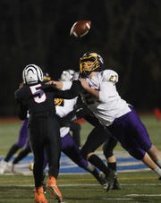 Tuckahoe's Michael Annunziata (5) fumbles the ball as he gets hit by Waterville's Darren Johnson (27) during the Class D state regional final at Mahopac High School Nov. 15, 2019.