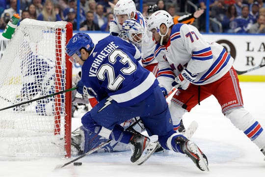 Tampa Bay Lightning center Carter Verhaeghe (23) gets knocked down by New York Rangers defenseman Tony DeAngelo (77) during the second period of an NHL hockey game Thursday, Nov. 14, 2019, in Tampa, Fla.
