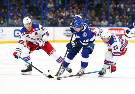 Nov 14, 2019; Tampa, FL, USA; Tampa Bay Lightning left wing Ondrej Palat (18) skates past New York Rangers center Chris Kreider (20) and New York Rangers defenseman Adam Fox (23) as he then scores a goal during the first period at Amalie Arena.