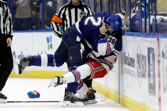Tampa Bay Lightning defenseman Luke Schenn (2) slams New York Rangers center Micheal Haley (38) into the boards as they fight during the second period of an NHL hockey game Thursday, Nov. 14, 2019, in Tampa, Fla.