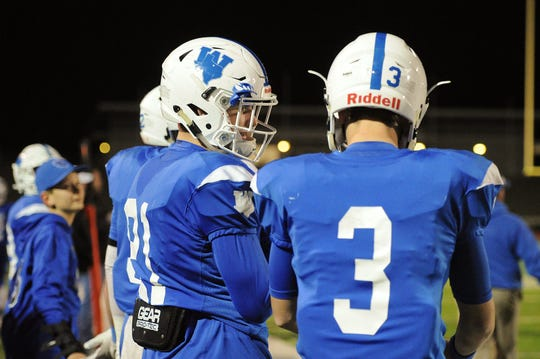 Awtry Blagg (left) and his quarterback Cy Belcher (right) talk on the sideline as they sit out the last minutes of the game, with Windthorst defeating Shamrock 53-16.