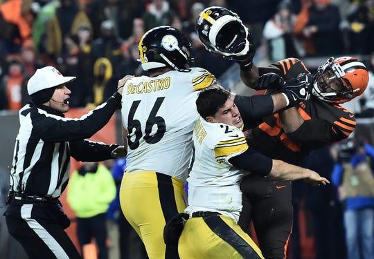Browns DE Myles Garrett hits Steelers QB Mason Rudolph with his own helmet.