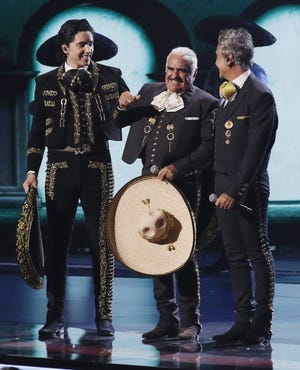 Alex Fernandez, left, Vicente Fernandez and Alejandro Fernandez  share a laugh after their performance at the 2019 Latin Grammys.