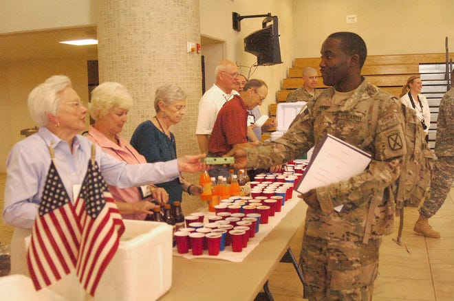 Sara Simmonds (left) hands out a warm apple pie and warm greetings to Staff Sgt. Markelle Tucker in 2011.