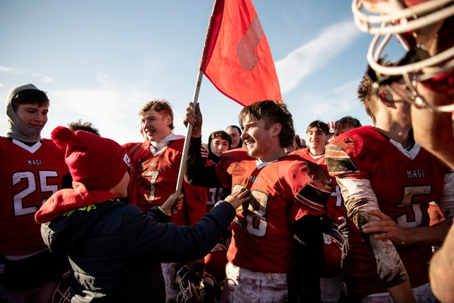 Colon junior Caiden Carver (28) waves the school flag after defeating Morrice 27-8 in the 8-player Division 1 state semifinal on Saturday, Nov. 16, 2019 at Colon High School in Colon, Mich.