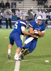 Southeastern quarterback Lane Ruby hands the ball off to running back Mikey Nusser during a Division VI regional semifinals game. Southeastern fell to Covington 36-20.