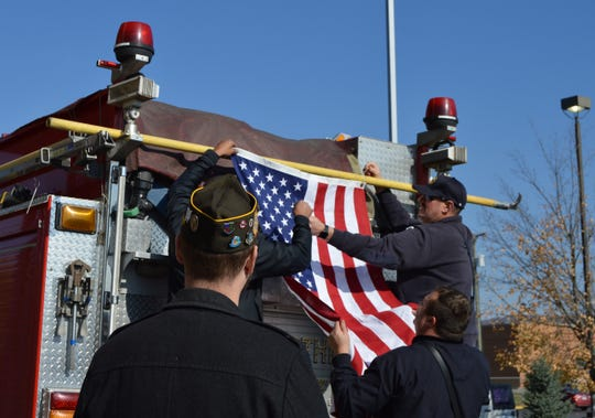 Members of the Chillicothe Fire Department and VFW Post 108 hang an American flag to honor the visit of Army Veteran Jeremy Miller in Chillicothe on Nov. 19.