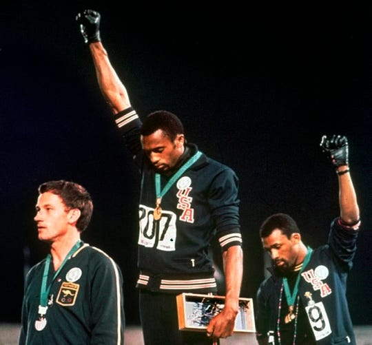In this Oct. 16, 1968, file photo, Australian silver medalist Peter Norman, left, stands on the podium as Americans Tommie Smith, center, and John Carlos raise their gloved fists in a human rights protest.