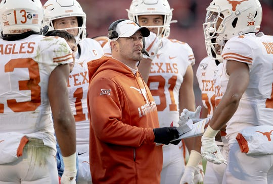Texas head coach Tom Herman looks at the replay of a touchdown catch by wide receiver Brennan Eagles (13) against Iowa State during an NCAA college football game on Saturday, Nov. 16, 2019, in Ames, Iowa.