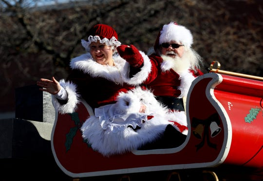 Mrs. Claus and Santa Claus on top of the sleigh waving to excited kids during the annual Wyandotte Christmas parade going down Biddle Avenue in downtown Wyandotte on Nov.16, 2019. Over 3,000 people crowded both sides of the sidewalk on Biddle Avenue to watch the parade on a sunny but cool morning.