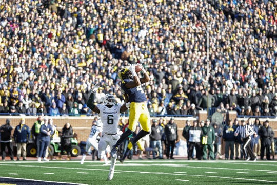 Nico Collins makes a catch over MSU's David Dowell during the fourth quarter Saturday.