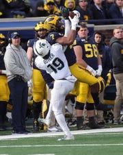 Michigan Wolverines receiver Tarik Black makes a catch against Michigan State cornerback Josh Butler during the second half Saturday, Nov. 16, 2019 at Michigan Stadium in Ann Arbor.