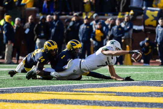Michigan State wide receiver Cody White reaches with the ball into the end zone as Michigan safety Josh Metellus (14) and cornerback Ambry Thomas tackle him in the first quarter of Michigan Stadium on  Nov. 16, 2019.