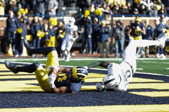 Michigan receiver Nico Collins scores a touchdown against Michigan State safety David Dowell during the second half at Michigan Stadium in Ann Arbor, Saturday, Nov. 16, 2019.