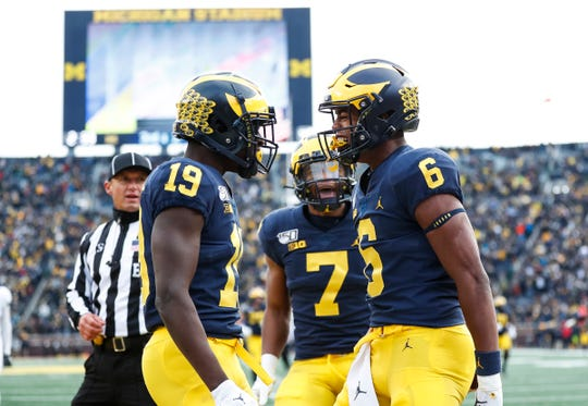 Michigan receivers Cornelius Johnson (6) celebrates his touchdown with Mike Sainristil (19) and Tarik Black (7) during the second half at Michigan Stadium in Ann Arbor, Saturday, Nov. 16, 2019.