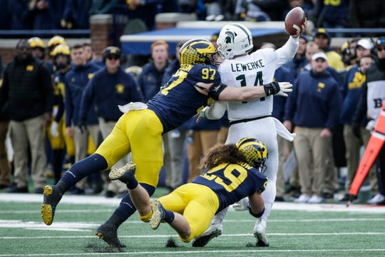 Michigan State quarterback Brian Lewerke is sacked by defensive lineman Aidan Hutchinson (97) and linebacker Jordan Glasgow (29) during the second half at Michigan Stadium in Ann Arbor, Saturday, Nov. 16, 2019.