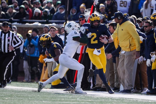 Michigan quarterback Shea Patterson is pushed out of bounds by Michigan State safety David Dowell during the first half at Michigan Stadium on Saturday, Nov. 16, 2019.