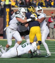 Michigan State linebacker Noah Harvey, left, and safety Xavier Henderson tackle Michigan wide receiver Ronnie Bell during the first half on Saturday, Nov. 16, 2019, at Michigan Stadium.