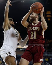 Elon's Andy Pack prepares to shoot over Michigan's Isaiah Livers on Friday.