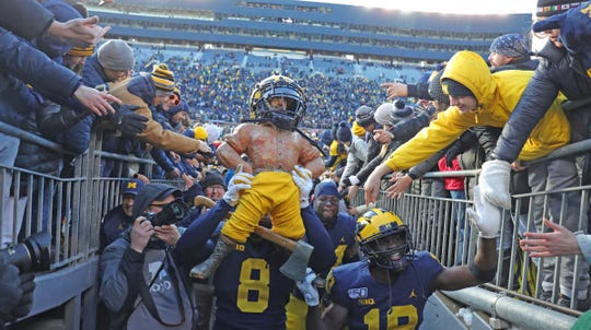 Michigan Wolverines' Devin Gil (8) and Mike Sainristil (19) carry the Paul Bunyan trophy off the field after the 44-10 win against the Michigan State Spartans, Saturday, Nov. 16, 2019 at Michigan Stadium in Ann Arbor.
