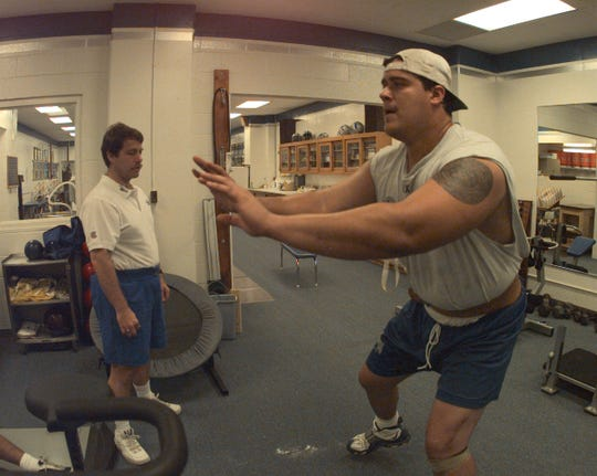 Detroit Lions offensive lineman Juan Roque strains against a strong rubber line as he works on his lateral movements for Joe Recknagel, assistant athletic trainer, in the Lions training room at the Pontiac Silverdome on May 29, 1998.