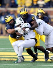 Michigan Wolverines' Carlo Kemp (2) and Kwity Paye (19) tackle Michigan State running back Elijah Collins during the second half Saturday, Nov. 16, 2019 at Michigan Stadium in Ann Arbor.