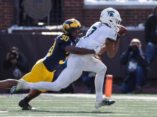 Michigan defensive back Daxton Hill tackles Michigan State receiver Cody White during the first half at Michigan Stadium on Saturday, Nov. 16, 2019.