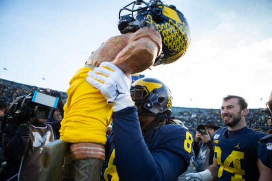 Michigan linebacker Devin Gil (8) carries the Paul Bunyan trophy off the field after the 44-10 win over Michigan State at Michigan Stadium in Ann Arbor, Saturday, Nov. 16, 2019.