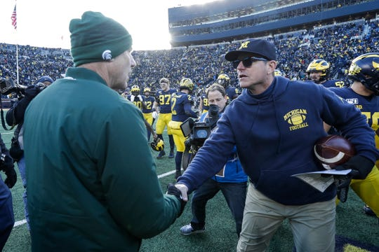 Mark Dantonio, left, shakes hands with Jim Harbaugh on Saturday after the game.