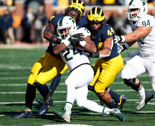 Michigan State running back Elijah Collins is stopped by Michigan linebacker Cameron McGrone (44) during the first half at Michigan Stadium on Saturday, Nov. 16, 2019.