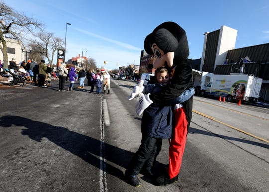 Many kids ran up to Mickey Mouse as he walked down Biddle Avenue during the annual Wyandotte Christmas parade in downtown Wyandotte, Michigan on November 16, 2019.Over 3,000 people crowded both sides of the sidewalk on Biddle Avenue to watch the parade on a sunny but cool morning.