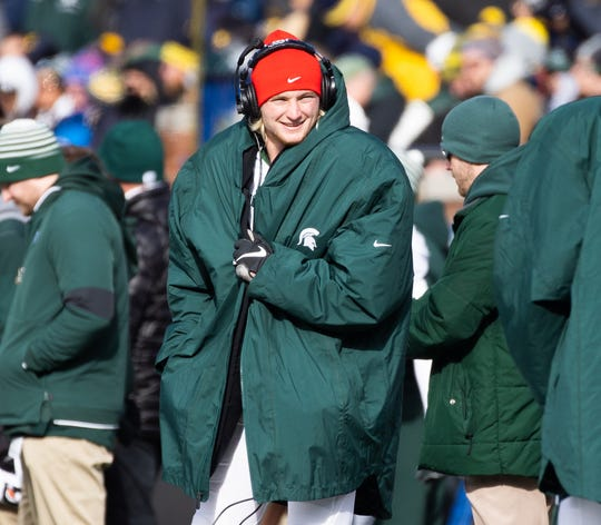 Michigan State Spartans quarterback Rocky Lombardi stays warm on the sideline during the game at Michigan Stadium on Saturday, Nov. 16, 2019.