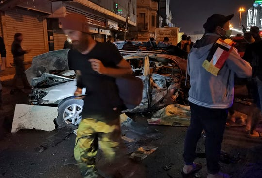 Anti-government protesters gather at the site of a bomb attack near Tahrir square in Baghdad, Iraq, Friday, Nov. 15, 2019. A bomb placed under a car exploded near the epicenter of anti-government protests in the capital, killed and wounded protesters, police and hospital officials said.