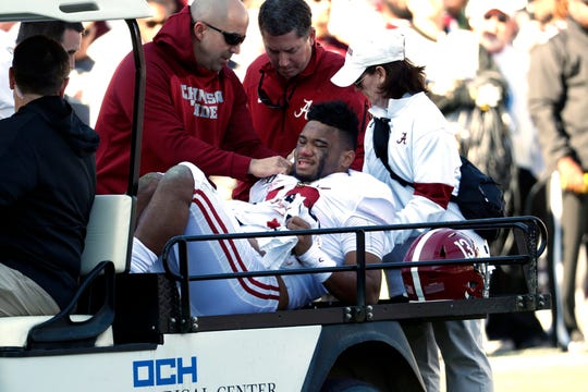 Alabama quarterback Tua Tagovailoa (13) is carted off the field after getting injured in the first half on Saturday.