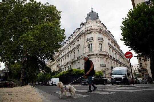 FILE - In this Aug.13, 2019 file photo, a man walks his dog next to an apartment building owned by Jeffrey Epstein in the 16th district in Paris, Tuesday, Aug. 13, 2019.