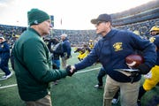 Michigan State head coach Mark Dantonio, left, and Michigan head coach Jim Harbaugh shake hands after the Wolverines defeated the Spartans, 44-10, Saturday at Michigan Stadium.