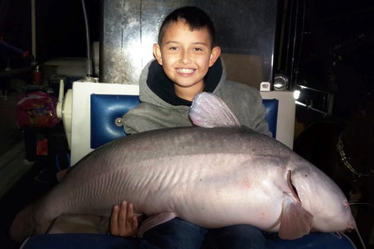 In this photo taken Nov. 10, 2019, Alex Flores, 9, holds a 42-pound blue catfish he caught while fishing in the New Mexico's Elephant Butte Reservoir.