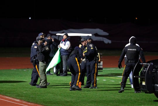 Police investigate the scene after a gunman shot into a crowd of people during a football game at Pleasantville High School in Pleasantville, N.J., Friday, Nov. 15, 2019.