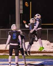 Walled Lake Western's C.J. Brown (3) celebrates a first-half touchdown with quarterback Zach Trainor (4).