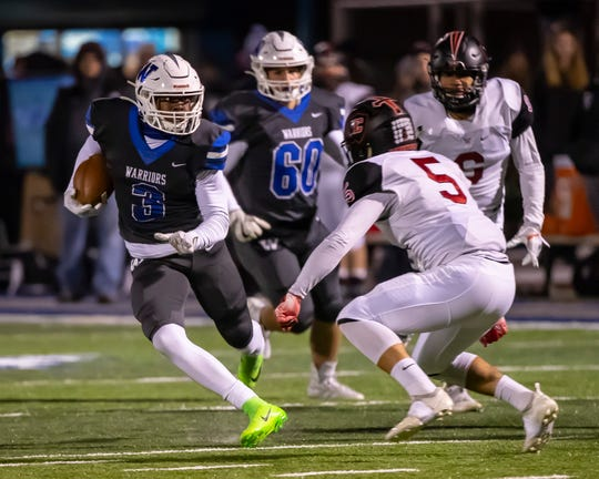 Walled Lake Western's CJ Brown (3) runs with the football in front of Livonia Churchill's Brendan Lowry (5).