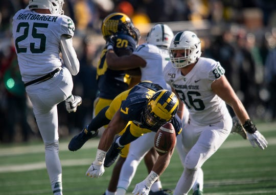 Michigan linebacker Khaleke Hudson blocks a fourth-quarter punt by Michigan State punter Josh Hartbarger.