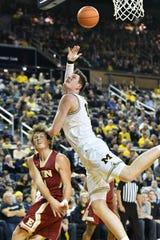 Michigan center Jon Teske (15) tries to put up a shot over Elon guard Zac Ervin (14).