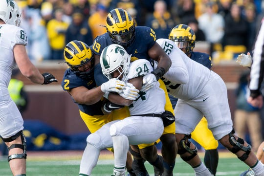 Michigan defensive linemen Carlo Kemp, let, and Kwity Paye tackle Michigan State running back Elijah Collins during the third quarter on Saturday.