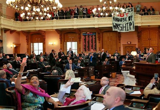 "FILE - In this April 10, 2019 file photo, some members of the Ohio House applaud following their vote while others photograph protestors who unfurled banners reading ""This is not a House of Worship"" and ""This is not a Doctor's office"" following a vote on the Heartbeat Bill at the Ohio Statehouse in Columbus, Ohio."